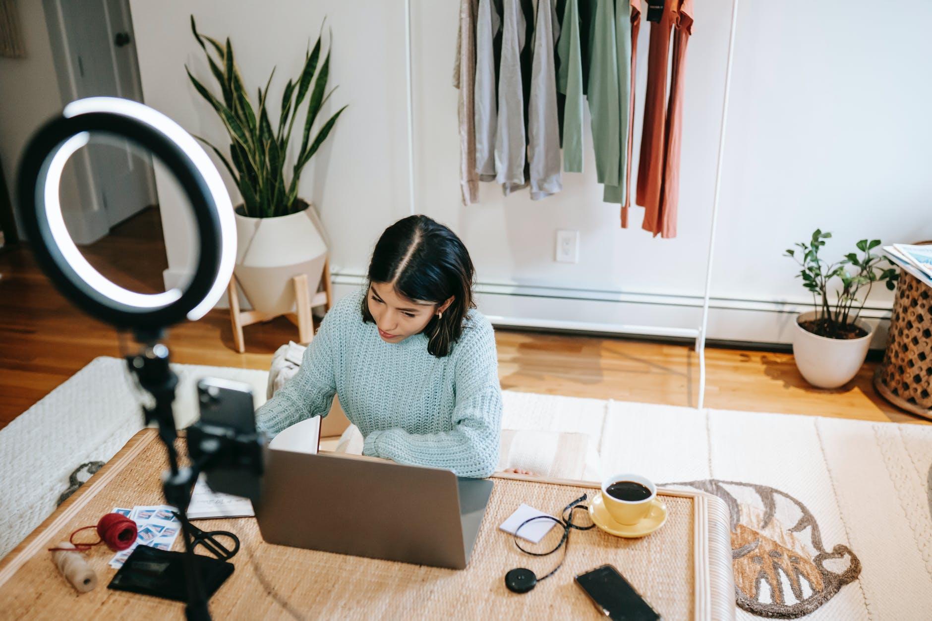 focused woman working at desk on laptop in studio