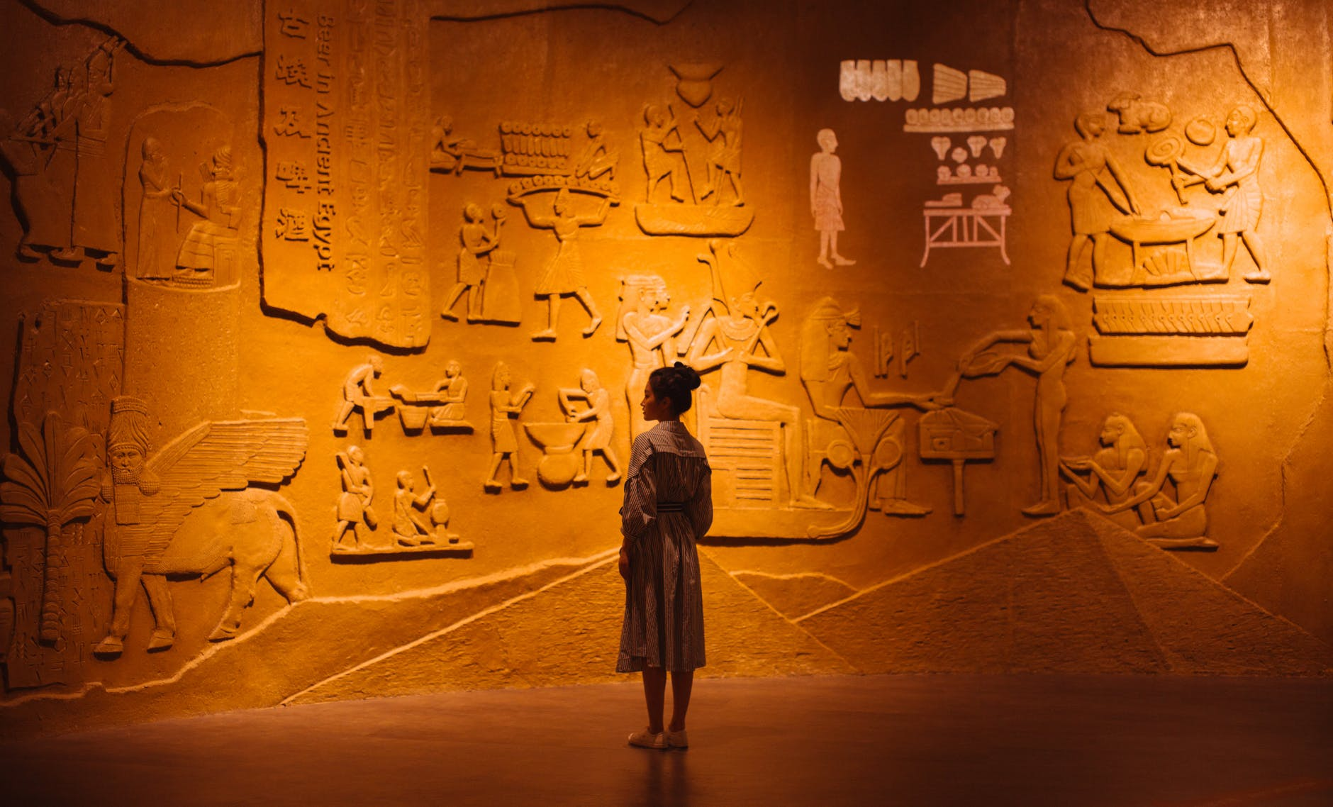 woman standing near old stone wall with carved images